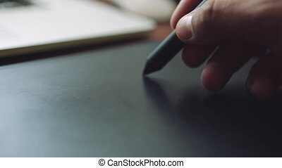 Designer working on a laptop with a graphics tablet. Closeup