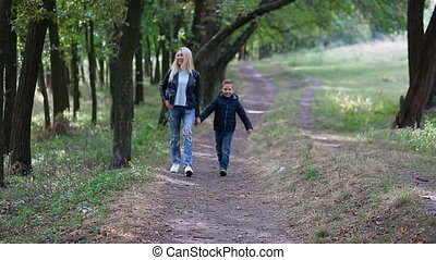 Mother and son walking in the park holding hands. Happy...