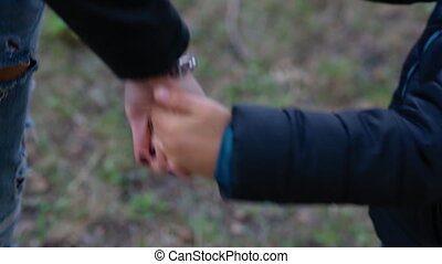 Mother and son holding hands. There is a toy airplane on the...