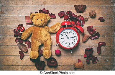 Vintage teddy bear toy and alarm clock with petals...