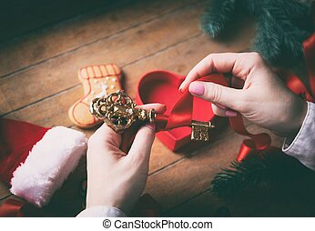 hands wrapping christmas golden key and gifts - Young woman...