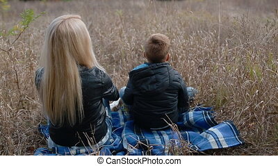 Mother and son sitting on the plaid outdoor, watching nature...
