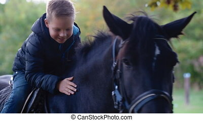 Happy kid on the horseback - Happy kid sitting on the...