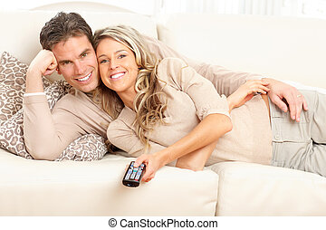 Young love couple - Young happy couple watching TV at home