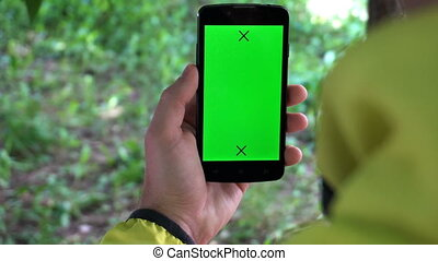 Closeup of male hands holding smartphone with green screen-prekeyed effects.nature in the background