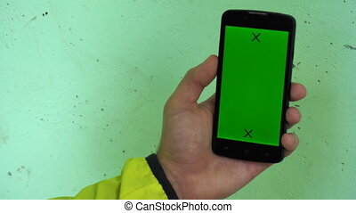 Closeup of male hands holding smartphone with green screen-prekeyed effects