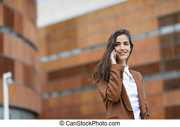 Young businesswoman talking with a smartphone in urban...