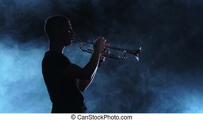 Professional musician man playing on trumpet. Smoky...