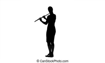 Girl musician playing on flute in slow motion. White studio...