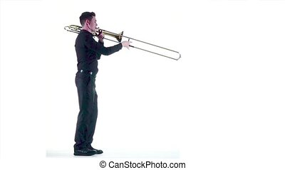 Trumpeter plays on wind instrument in white studio. Slow...