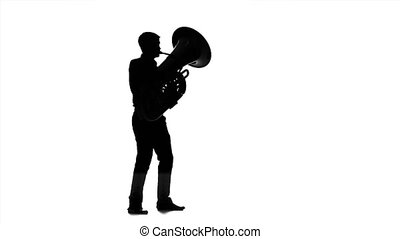 Man musician playing on tuba in slow motion. Black silhouette
