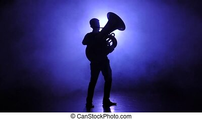 Trumpeter man in smoky studio plays on tuba, slow motion -...