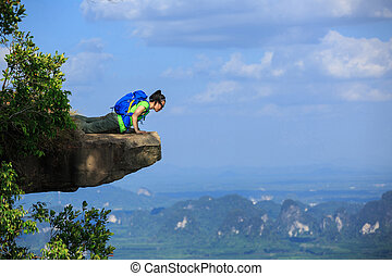successful woman hiker lying on mountain cliff looking down