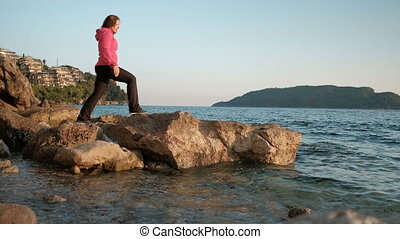 woman walking on lake shore, Step from stones looking into distance