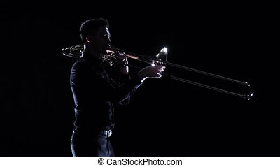 Musician plays on wind instrument melody in dark. Slow...