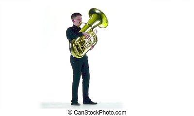 Man plays on tuba melody in white studio. Slow motion - Man...