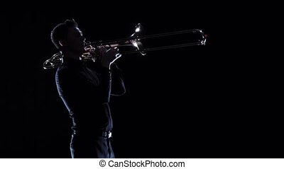 Trumpeter plays on wind instrument melody in dark. Slow...
