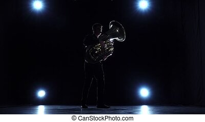 Musician in dark with spotlights playing tuba jazz. Slow...