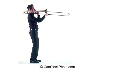 Trumpeter plays on wind instrument in slow motion. White...