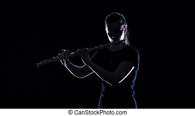 Female musician blows motif in flute in slow motion. Studio...