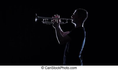 Man blows motif in wind instrument. Black studio, slow...