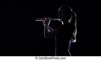 Woman musician blows the motif in wind instrument. Slow...