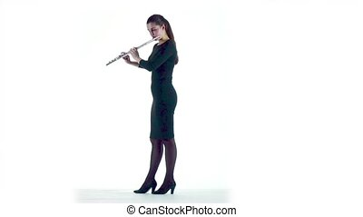Woman plays on flute melody in white studio. Slow motion -...