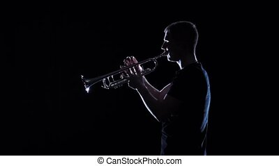 Man blows motif on wind instrument in slow motion. Studio -...