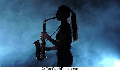 Silhouette musician female playing on saxophone. Smoky...
