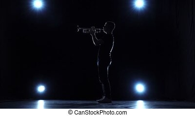 Musician in studio with spotlights playing trumpet jazz....
