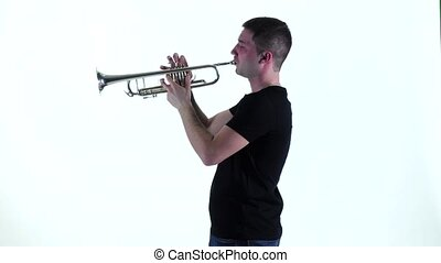 Young musician playing on pipe standing sideways in slow...