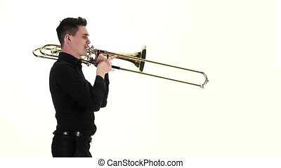 Young musician playing on trombone standing sideways in slow...