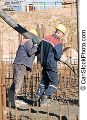 workers on concrete works - two builder workers aiming pump...