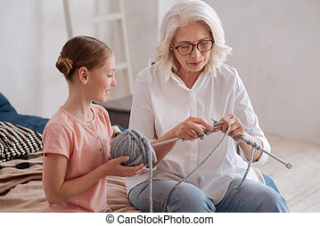 Positive nice woman teaching her granddaughter to knit -...