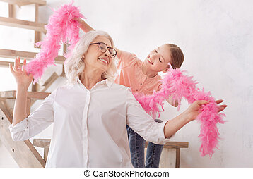 Happy cute girl helping her grandmother to wear a feather...