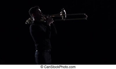 Trumpeter plays on wind instrument tranquil melody in slow...