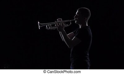 Melody in slow motion plays man trumpeter. Black studio...