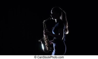 Brunette playing on saxophone standing sideways. Slow...