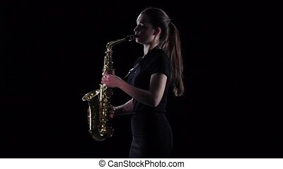 Brunette plays on saxophone in slow motion. Black studio...