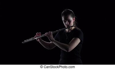 Woman plays on flute slow melody. Black background, slow...