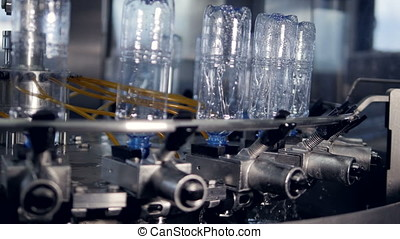 Numerous bottles being washed at bottled water plant. - The...