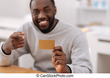 Credit card being held by a positive nice man