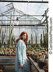 Young girl standing in a glass house full of cacti -...