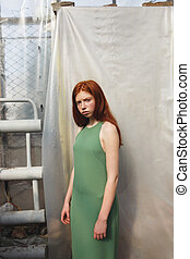 Serious redheaded woman in dress and looking at camera...