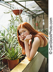 Portrait a beautiful redheaded woman in dress leaning on a...