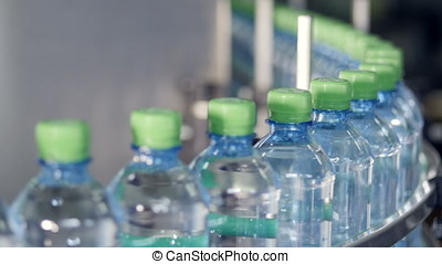 PET bottles filled with water moving on a conveyor. -...