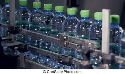Industrial conveyor transporting plastic bottles with water....