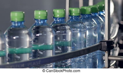 Capped bottles filled with water moving on a conveyor. -...