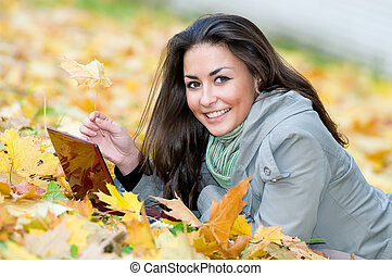 Happy student girl lying in autumn leaves with netbook - One...