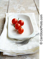 Tomatoes Cherry - Sprig of cherry tomatoes on a white plate...